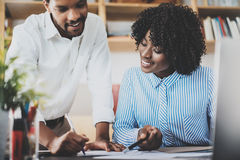 Two young coworkers working together in a modern office.Black business people discussing new startup project.Horizontal. Blurred stock photography