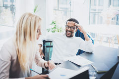 Two young coworkers working together in a modern office.Black man wearing glasses, looking at the businesswoman and. Two young coworkers working together in a Royalty Free Stock Photos