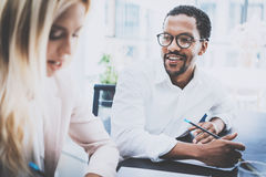 Two young coworkers working together in a modern office.Black man wearing glasses, looking at the businesswoman and. Two young coworkers working together in a Stock Photos