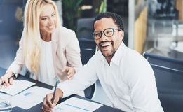 Two young coworkers working together in a modern office.Man wearing glasses, looking at the camera and smiling.Woman discussing wi Royalty Free Stock Photography