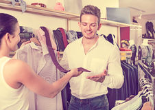 Two young customers selecting shirt and tie. At the clothing shop Stock Photo