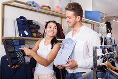 Two young customers selecting shirt and tie. In the clothing shop. Focus on both persons Royalty Free Stock Photography