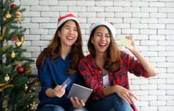 Two young cute asia women holding tablet and credit card while s stock images