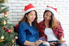 Two young cute asia women holding tablet and credit card while shopping online with happiness, Christmas holiday shopping concept royalty free stock image
