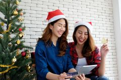 Two young cute asia women holding tablet and credit card while shopping online with happiness, Christmas holiday shopping concept stock photography