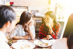 Two young and cute Asian women talking and laughing together during lunch time. royalty free stock images