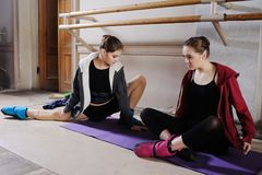 Two young cute ballerinas do stretching before training or rehearsal stock images