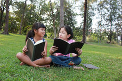 Two young cute girls reading. Stock Photo