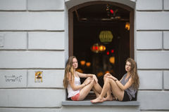 Two young cute girls sitting at the window of a nightclub. Fun. Stock Photography