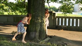 Two young cute teen girls play indulge in the Park, run around the tree. Two cute teen girls play indulge in the Park, run around the tree stock footage