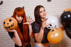 Two young cute women with pumpkin and painted balloons frighten. Somebody over Halloween decorations royalty free stock images