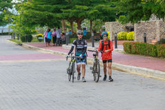 Two young cyclists with their bicycles walking together after bike touring at the dam. Stock Images