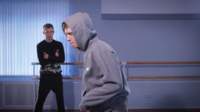 Two young dancers in the training hall. The guy in a sovbodny sweater works the main movements in a breakdance. And his. Opponent on command costs and looks at stock video footage