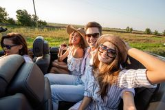 Two young dark-haired women in hats are sitting young with man in a black cabriolet and smiling on a summer day. royalty free stock images