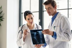Two young dedicated doctors analyzing together the radiograph of a patient. Two young dedicated doctors analyzing together the radiograph of the leg of a patient Stock Image