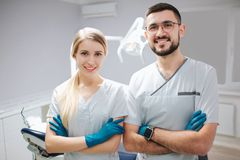 Two young dentist professionals in dentistry room. They pose on camer and smile. People hold hands crossed. Two young dentist professionals in dentistry room stock images