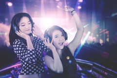 Two young DJ in the night party. Picture of two beautiful young DJ looks happy while playing music for people in the night party Stock Photo