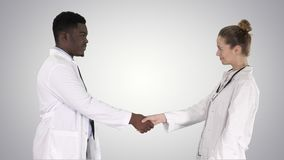Two young doctor shaking hands on gradient background. stock video