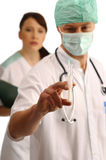 Two young doctors. Doctor in mask and cap with stethoscope and injection, young nurse in behind Royalty Free Stock Photo