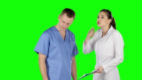 Two young doctors debating. Green screen. Two young doctors debating, young medical staff talking together, scolds assistant, intern frustrated looks down stock footage