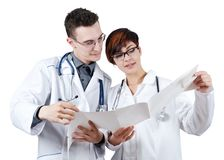 Two young doctors discuss the results of the electrocardiogram. Isolated on white Royalty Free Stock Images