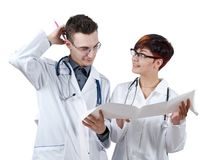 Two young doctors discuss the results of the electrocardiogram. Isolated on white Royalty Free Stock Photography