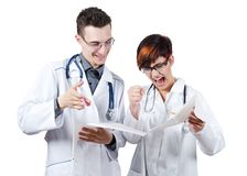Two young doctors discuss the results of the electrocardiogram. Isolated on white Royalty Free Stock Photo