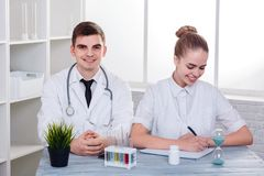 Two young doctors guy and girl, sitting at the desk and smiling, the girl writes something. Two young doctors in white uniform guy and girl, European appearance Royalty Free Stock Photography