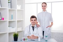 Two young doctors, a guy and a girl, in a white medical gown, smile happily. The concept of medicine. Two young doctors, a guy and a girl, dressed in a white Royalty Free Stock Photos