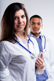 Two young doctors. Half body portrait of two smiling doctors, studio background Royalty Free Stock Images