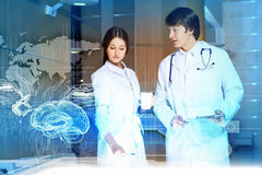 Two young doctors. Image of two young doctors examining futuristic image of brain Stock Photography