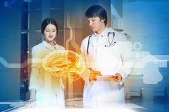 Two young doctors. Image of two young doctors examining futuristic image of brain Royalty Free Stock Images