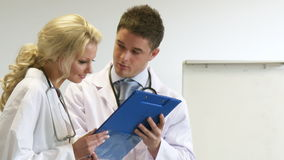 Two young doctors looking at a clipboard stock footage