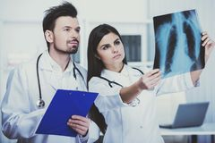 Two young doctors are looking at roentgen in clinic. Medical staff Royalty Free Stock Photography