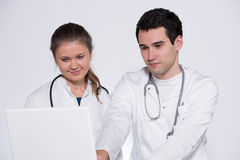 Two young doctors. Male and female in white coats, with stethoscope working with laptop pc Royalty Free Stock Images