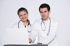 Two young doctors. Male and female in white coats, with stethoscope working with laptop pc Royalty Free Stock Photo