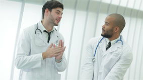 Two young doctors in medical gown lively debating stock video