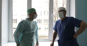 Two young doctors in medical uniforms and masks are talking in the hospital against the window. stock footage
