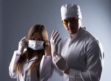 Two young doctors preparing for operation in contrasting light Stock Photography