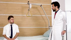 Two young doctors sitting in a hospital room. And chatting with each other. They are laughing at the end stock video