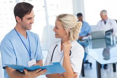 Two young doctors talking about a blue file. In front of two doctors Stock Photography