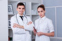 Two young doctors in a white medical robe posing standing. The concept of medicine. Two young doctors, a guy and a girl dressed in a white medical robe posing Stock Image