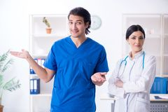 The two young doctors working in the clinic stock images