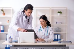 Two young doctors working in the clinic stock images