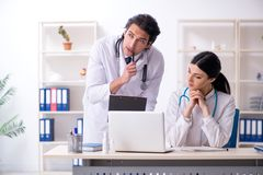 The two young doctors working in the clinic stock photography