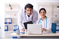 Two young doctors working in the clinic stock photo