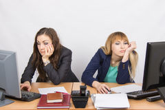 Two young employee of the office behind a desk looking sadly into the frame Stock Photo