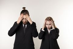 Two young employees in black suits standing with hands on head, laid-off workers after bankruptcy of their company royalty free stock image