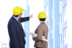 Two young engineers with blueprints in front of th Stock Image