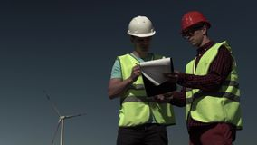Two Young Engineers Men Approach A Windmill stock footage
